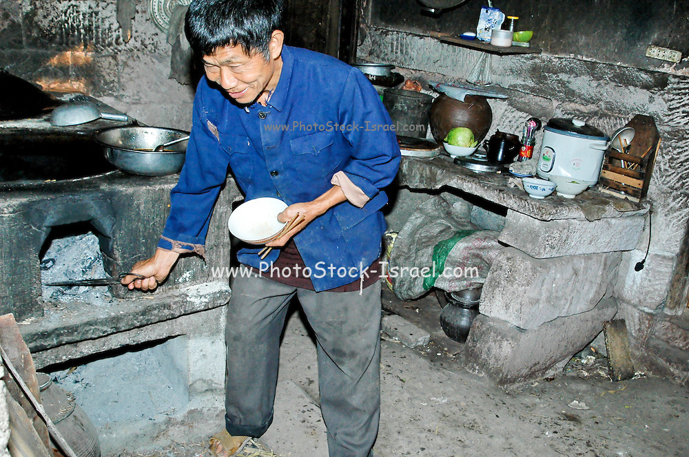 China, man cooks in a Rural kitchen