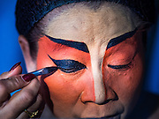 17 FEBRUARY 2016 - BANGKOK, THAILAND: A performer puts on her makeup before a Chinese opera performance in Bangkok. She's a member of a small troupe that travels from Chinese shrine to Chinese shrine performing for a few nights before going to another shrine. They spend about half the year touring in Thailand and the other half of the year touring in Malaysia. Members of the troupe are paid about 5,000 Thai Baht per month (about $140 US). Chinese opera was once very popular in Thailand, where it is called Ngiew. It is usually performed in the Teochew language. Millions of Chinese emigrated to Thailand (then Siam) in the 18th and 19th centuries and brought their culture with them. Recently the popularity of ngiew has faded as people turn to performances of opera on DVD or movies. There are still as many 30 Chinese opera troupes left in Bangkok and its environs. They are especially busy during Chinese New Year and Chinese holiday when they travel from Chinese temple to Chinese temple performing on stages they put up in streets near the temple, sometimes sleeping on hammocks they sling under their stage. Most of the Chinese operas from Bangkok travel to Malaysia for Ghost Month, leaving just a few to perform in Bangkok.     PHOTO BY JACK KURTZ
