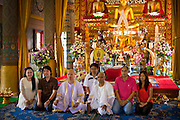 28 JUNE 2011 - CHIANG MAI, THAILAND:   Family members sit with men being ordained as Buddhist monks for photos at at Wat Phrathat Doi Saket a large temple complex in Chiang Mai, Thailand. The temple at Doi Saket is said to have been built in the year 1112, but it has been renovated several times since then. Most Thai males enter the Buddhist clergy, called the Sangha, at least once in their lives. Their stay in the monastery can be as short as one week or a lifetime committment, depending on the man.   PHOTO BY JACK KURTZ
