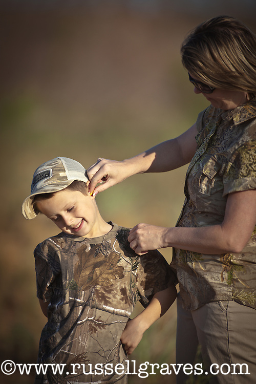 MOTHER PUTTING EARLPUGS IN THE EARS OF A YOUNG DOVE HUNTER REALTREE CAMOUFLAGE