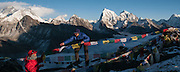 Nepal, Khumbu, Everest region, Gokyo Ri, Marie Jeanne Miniscloux and Pasang Sherpa putting up Tibetan prayer flags, Everest  8850m is behind Arkam Tse 6423m and Cholotse 6335m are on the right