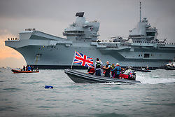 © Licensed to London News Pictures. 16/08/2017. Portsmouth, UK. A flotilla of small boats follows the Royal Navy's new aircraft carrier HMS Queen Elizabeth as she enters her home port of Portsmouth for the first time. The new ship at 65,000 tonnes is the biggest warship ever built in the UK. Photo credit: Peter Macdiarmid/LNP