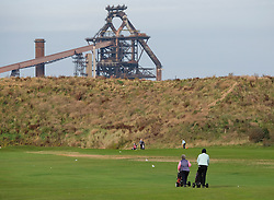 © Licensed to London News Pictures.20/10/15<br /> Redcar, UK. <br /> <br /> People play golf at Cleveland golf club in front of the recently closed SSI UK steel blast furnace in Redcar, England. The closure of the site marks the end of 170 years of steel making heritage on Teesside and was the first of a number of recent closures of steel making plants across the UK.<br /> <br /> Photo credit : Ian Forsyth/LNP