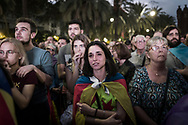 """Outside the Parliament building, pro-independence supporters stand in  confusion as they watch on giant screens Catalan President Carles Puigdemont who appeared to declare independence from Spain, then immediately suspending that decision to allow for more """"dialogue"""" with leaders in Madrid. October 10, 2017 in Barcelona, Spain"""