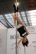 A young woman is performing pole dance by her stand, sponsoring 'Pole Addicts',at the Erotica 2006 show in London, UK, on Friday, Nov. 17, 2006. Erotica is the world's largest adult lifestyle show. It attracts about 80,000 visitors every year with its over 150 retailer exhibitors, dazzling and decadent transvestite cabaret shows, fun foreplay seminars, beautiful lingerie collections, art and fetish demonstrations. **Italy Out**