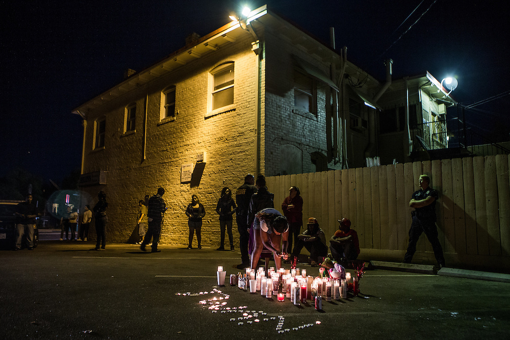Members of Stockton's Community Response Team question mourners at the site of a memorial for five people shot the night before in Stockton, California, September 18, 2013. Facing stark and rising homicide rates, the California cities Oakland and Stockton are taking a second chance at a novel method of disrupting street gangs, called Ceasefire, in which the police use social-analytics software to map out connections between a city's most violent gang members, using the data to make targeted and coordinated arrests.