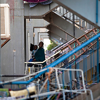 "A Sudanese refugee carying a baby climbs the stairs in the SinSin building on February 28 2011 in Eilat. The municipality hung 1,500 red flags around the city as a sign of warning and put up hundreds of banners reading: ""Protecting our home, the residents of Eilat are drawing the line on infiltration."" Eilat Mayor Meir Yitzhak Halevi said that 10 percent of the city's population was currently made up of migrants and that the residents feel that the city has been conquered...Photo by Olivier Fitoussi."