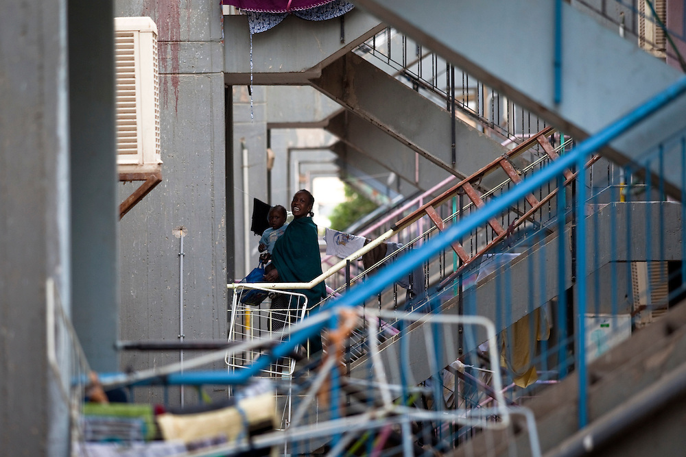 """A Sudanese refugee carying a baby climbs the stairs in the SinSin building on February 28 2011 in Eilat. The municipality hung 1,500 red flags around the city as a sign of warning and put up hundreds of banners reading: """"Protecting our home, the residents of Eilat are drawing the line on infiltration."""" Eilat Mayor Meir Yitzhak Halevi said that 10 percent of the city's population was currently made up of migrants and that the residents feel that the city has been conquered...Photo by Olivier Fitoussi."""