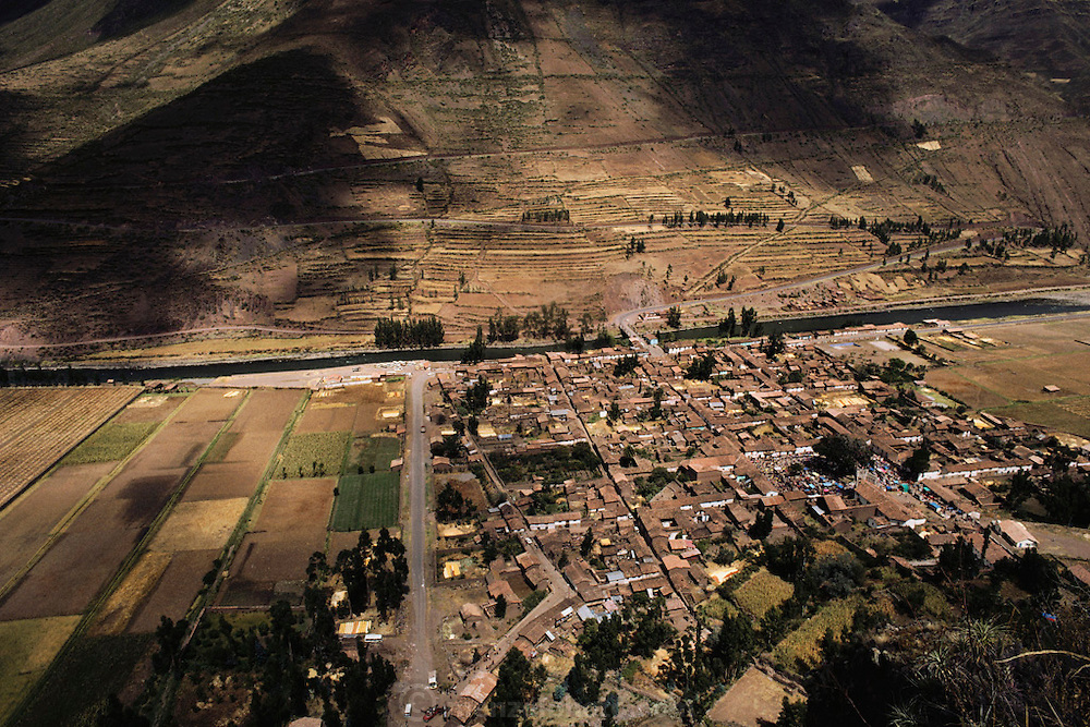 Pisac, Peru, seen from the Inca ruins on the hill overlooking the town in the Urubamba Valley, the Sacred Valley of Incas. Sunday market is in full swing in central plaza of the town. Wide view of town.