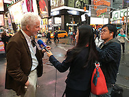 NYC, NY, USA. 19th Nov. 2015. Reporter from NTD China News (New Tang Dynasty) interviews man in Times Square, the day after an ISIS propaganda video came out threatening New York City, particularly Times Square. NYC's Mayor and Police Commissioner both said there is no specific and credible threat against New York City.