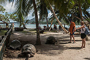 Tourists interact with Aldabra Giant Tortoises, a main attraction on the island of Curieuse, Seychelles on February 20, 2018. Tourism is one of the country's main income generators.<br /> <br /> The government of Seychelles has created 81,000 square miles of Marine Protected Areas as part of a conservation debt swap deal in an effort to shield marine ecosystems from unsustainable development and climate change while safeguarding its economy.