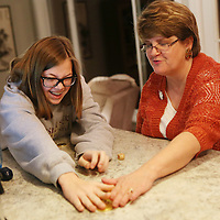 Lauren Wood | Buy at photos.djournal.com<br /> Lindsey Nelson Newhall, 16, left, laughs with her mother Rebecca after the dreidel landed on gimel, meaning the player gets the pot of gelt, or chocolate coins, on Dec. 6, the first night of Hanukkah at Mimi VanDevender's Tupelo home.