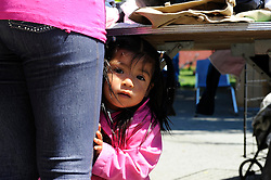 A child peers out from under a table as her mother goes over clothes given out at St. Clare's Corner, established in Salinas by the Franciscan Workers of Junipero Serra in 1982. Supplied by the Food Bank of Monterey County, basic foodstuffs like rice and beans supplement family diets from October to May, the winter months when unemployment is highest.