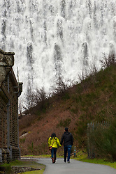 © Licensed to London News Pictures. 06/01/2018. Elan Valley Reservoirs, Powys, Wales, UK.  A young couple visit as water rages over the Caban Coch dam near Rhayader, Powys, Wales. The Elan Valley reservoir complex has been replenished after heavy rainfall from Storm Eleanor and melting snow which fell in December 2017. Birmingham's Frankley reservoir is supplied by Elan Valley reservoirs on a gravity feed over a distance of 73 miles (117 Km.) Photo credit: Graham M. Lawrence/LNP