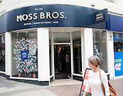Woman walking past Moss Bros shop in central Ipswich, Suffolk, England, UK