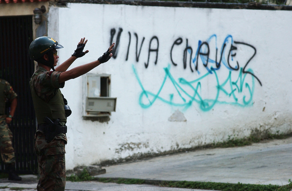 "Members f the national guard try and control a protest near the Cuban embassy.  The sign reads ""Long live Chavez"".  Opposition to President Hugo Chavez  gathered at the embassy to protest the recent arrests in Cuba as well as what they view as the ""cubanization"" of Venezuela.  Chavez supporters also came to express their views and the two groups clashed, throwing rocks and bottles."