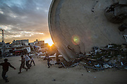 Childrens playing soccer next to the rubble of a water reservoire in Khuza's