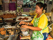 23 DECEMBER 2015 - BANGKOK, THAILAND: A vendor makes Thai style peanut brittle in her street stall in the Banglamphu Market. Banglamphu Market (also spelled Bang Lamphu) is close to Bangkok's backpacker haunts of Khao San Road. The market is a popular place for knock off designer clothes and street food. The market is an informal collection of street stalls and sidewalk vendors. Bangkok city officials have plans to evict the vendors, close the market and gentrify the neighborhood. This would follow closing similar markets on Maharat Road and Saphan Lek.       PHOTO BY JACK KURTZ