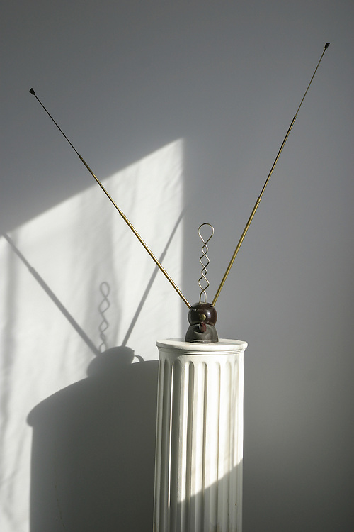 old fashioned rabbit ears antenna on fluted pedestal casts shadow on wall