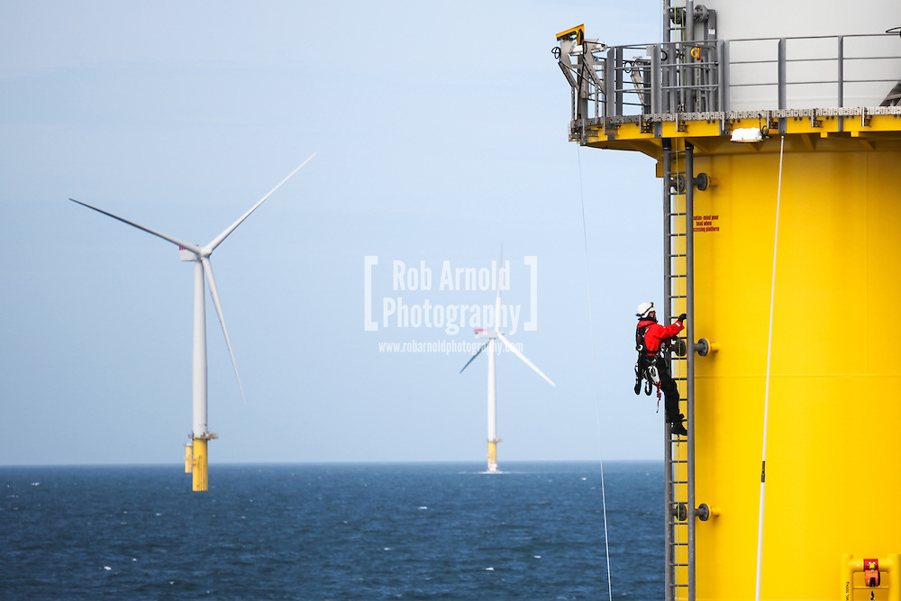 © Rob Arnold.  09/04/2014. North Wales, UK. A man climbing the ladder of a wind turbine on the Gwynt y Môr Offshore Wind Farm off the coast of North Wales. Photo credit : Rob Arnold