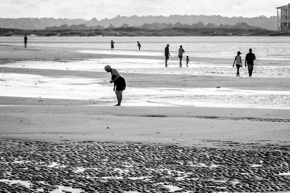 A telephoto lens creates an interesting backlit composition of people searching for sea shells early in the morning at Ocean Isle Beach, NC. Across the channel is Holden Beach.