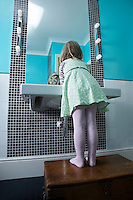 Girl (3-4) standing on wooden chest to reach bathroom sink