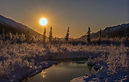 Nearly full supermoon sets over the Chugach Mountains and Chugach State Park in Southcentral Alaska. Winter. Morning.