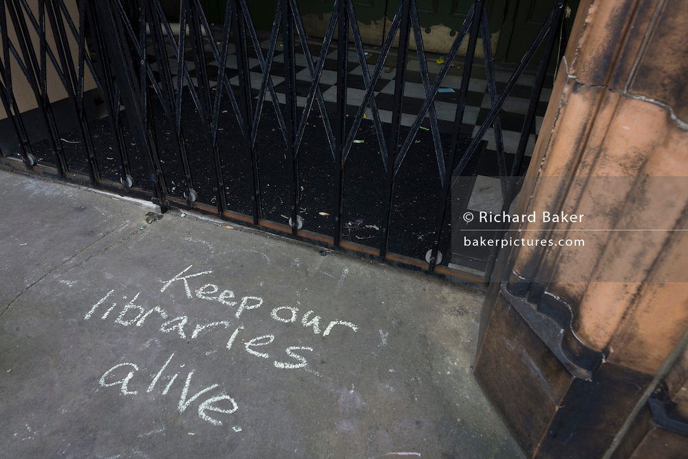 Campaigners locked out of the closed Carnegie Library have written messages in chalk on the front steps in Herne Hill, south London on 7th May 2016. For ten days, members of the community in the south London borough occupied their important resource for learning and social hub for the weekend. But after a long campaign by locals, Lambeth have gone ahead and closed the library's doors because they say, cuts to their budget mean millions must be saved. A gym is planned to replace the working library and while some of the 20,000 books on shelves will remain, no librarians will be present to administer it. London borough's budget cuts mean four of its 10 libraries will either close, move or be run by volunteers.