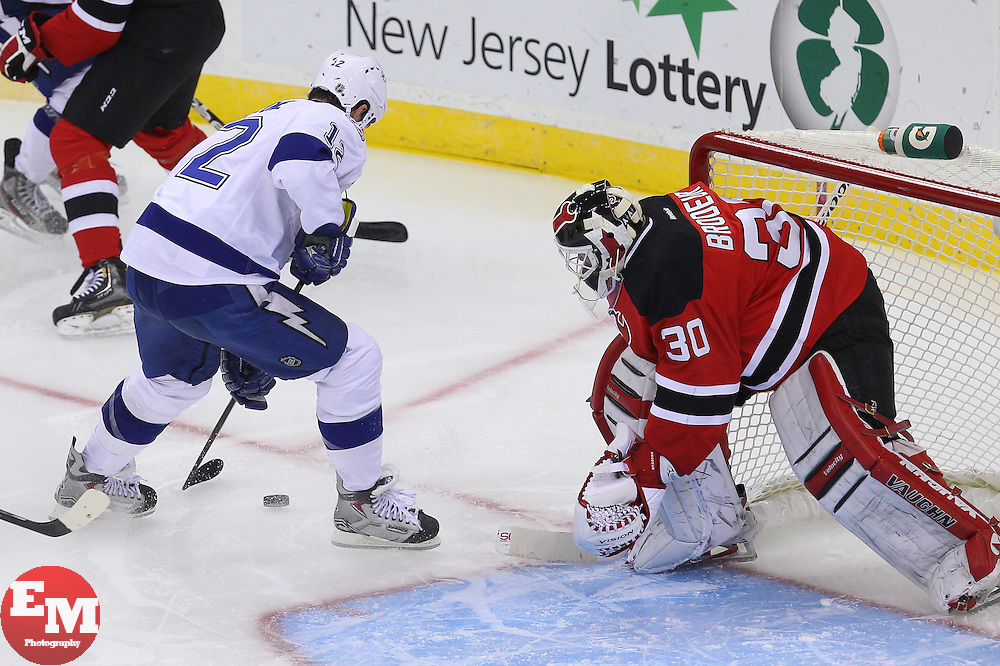 Feb 7, 2013; Newark, NJ, USA; Tampa Bay Lightning left wing Ryan Malone (12) skates with the puck by New Jersey Devils goalie Martin Brodeur (30) during the third period at the Prudential Center. The Devils defeated the Lightning 4-2.
