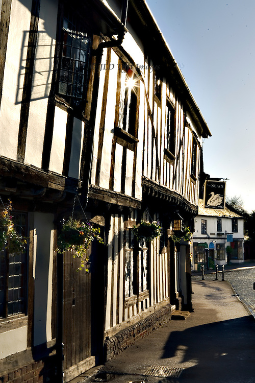 Lavenham townscapes and Tudor period architecture.  igh Street entrance facade of the Swan Inn, seen from a sharp angle alongside the structure to emphasize the second storey overhang.