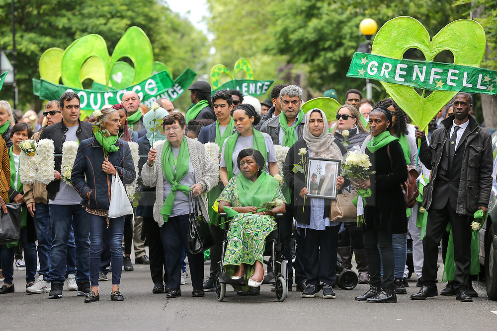 © Licensed to London News Pictures. 14/06/2019. London, UK.  Survivors, family and friends of the victims wear symbolic green scarf take part in a silent procession marching from St Helen's Church to Grenfell Tower to commemorate the second anniversary of the Grenfell Tower fire. On 14 June 2017, just before 1:00am a fire broke out in the kitchen of the fourth floor flat at the 24-storey residential tower block in North Kensington, West London, which took the lives of 72 people. More than 70 others were injured and 223 people escaped. Photo credit: Dinendra Haria/LNP