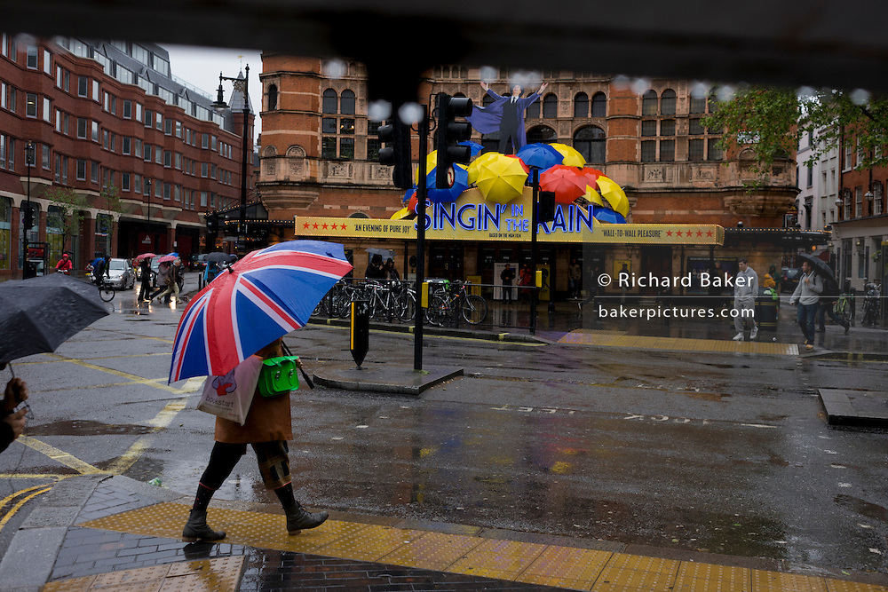 On a rainy day, pedestrians hurry past during a shower outside where the musical Singing in the Rain is playing.