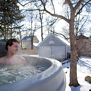 Aurelien believes that the best thing after surfing is relaxing in his hot tub and enjoying a drink. Here, he is outside of his Rochester home smiling at his wife who just pulled into their driveway.