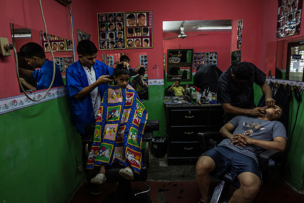 SAN PEDRO SULA, HONDURAS - MAY 23, 2014: Mayor David Dubon, 17, (left) works as a barber cutting his nephew's hair.  Dubon tried to go to the United States illegally, but got deported.  He has had several member of his family murdered, and wants to flee the violence. He is working as a barber until he can save enough money to try the trip again.  PHOTO: Meridith Kohut for The New York Times.