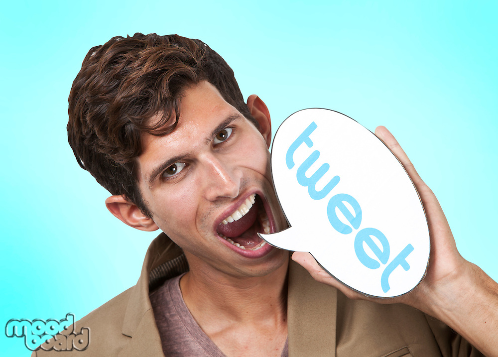 Portrait of young man holding tweet word bubble against white background
