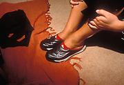 Pair of legs wearing Nike trainers on feet.