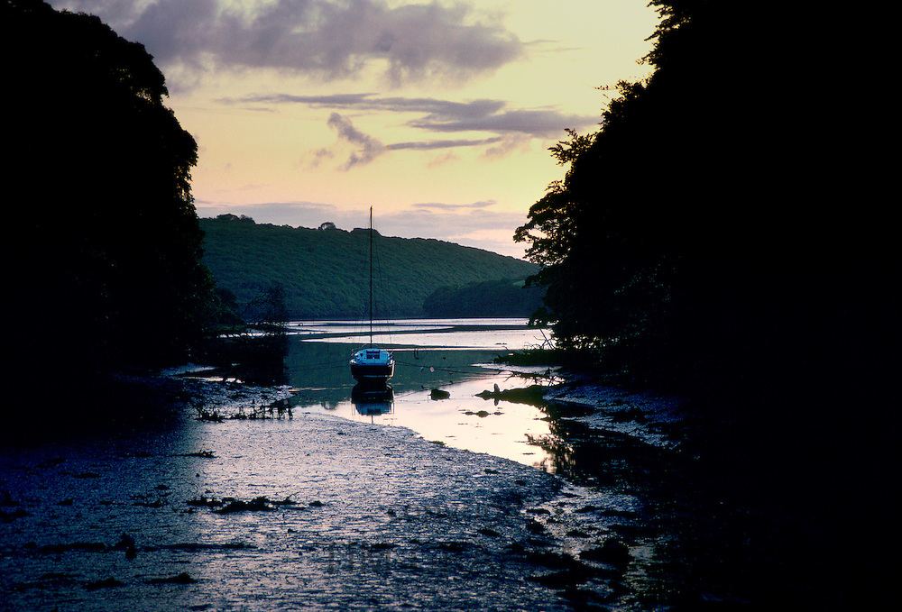 A view at dawn of a sailing boat moored at low tide on the Helford River at Trelowarren Mills, Cornwall, United Kingdom.