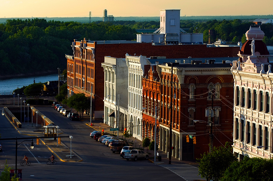 The 1800's Italianate architecture of the lower Commerce Street historic district in Montgomery, Alabama is illuminated by the setting sun.