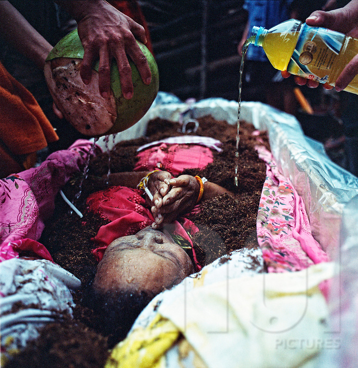 Funeral ceremony, Vientiane Province, Laos. The dead body, an old woman, lays in the coffin.