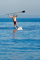 A mid adult man falling off a stand up paddle board.