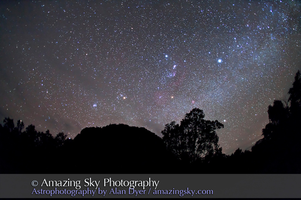 Northern winter constellations including Orion over Timor Rock with Sirius at right and Pleiades  and Aldebaran at left. Shot near Coonabarabran, NSW, Australia, December 6, 2010. Taken with Canon 5D MkII camera and 15mm lens, for 45 seconds at f/2.8 and ISO 3200.