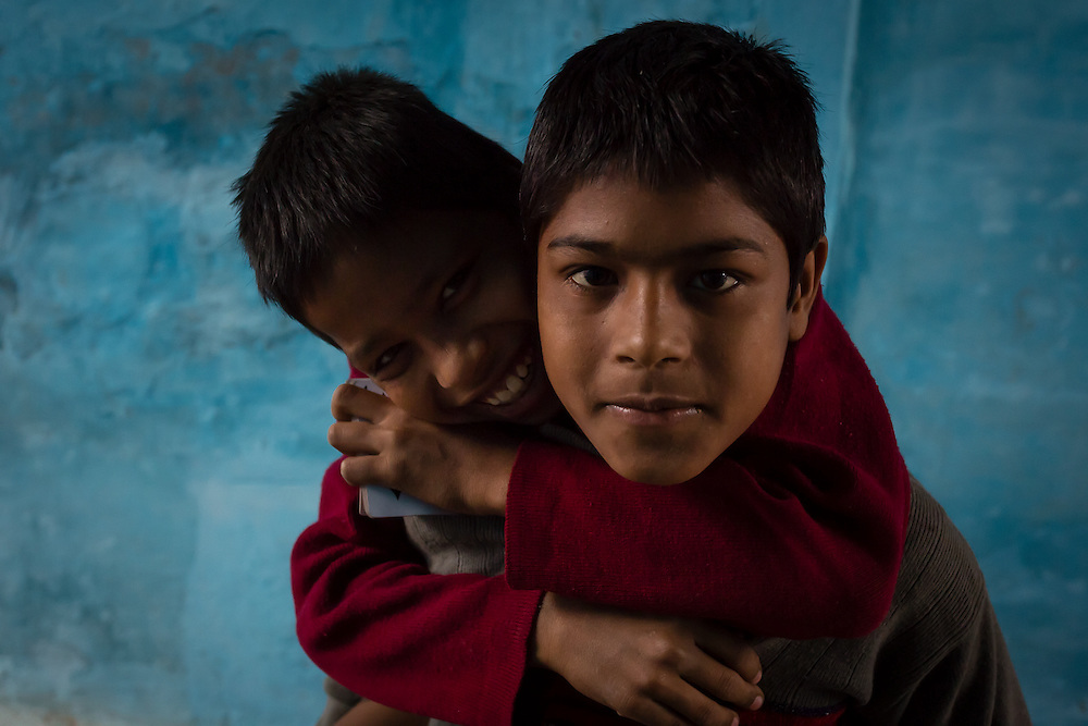 These two brothers were playing cards outside their home. When they saw me, they started posing for the camera. Suddenly the younger one just jumped to his brothers back for an improvised piggyback ride.