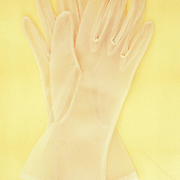 Pair of white nylon ladies see-through gloves lying on antique paper