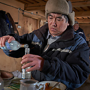 "Kim Pomishin, a shaman at a Buryati village in Selenga in the Kabansk region along the shore at Russia's Lake Baikal, uses vodka to prepare for a ritual. Crowned the ""Jewel of Siberia"", Baikal is the world's deepest lake, and the biggest lake by volume, holding 20% of the world's fresh water. In the winter, the lake 31,722 square meter surface is entirely frozen with ice averaging 2 meters thick."