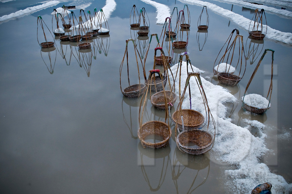 Empty wicker baskets lay down in Doc Let salt marsh waters. Vietnam, Asia