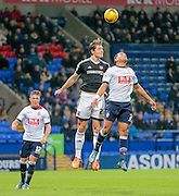 Prince-Desire Gouano (Bolton)and Lass Vibe (Brentford) jump for the ball during the Sky Bet Championship match between Bolton Wanderers and Brentford at the Macron Stadium, Bolton, England on 30 November 2015. Photo by Mark P Doherty.