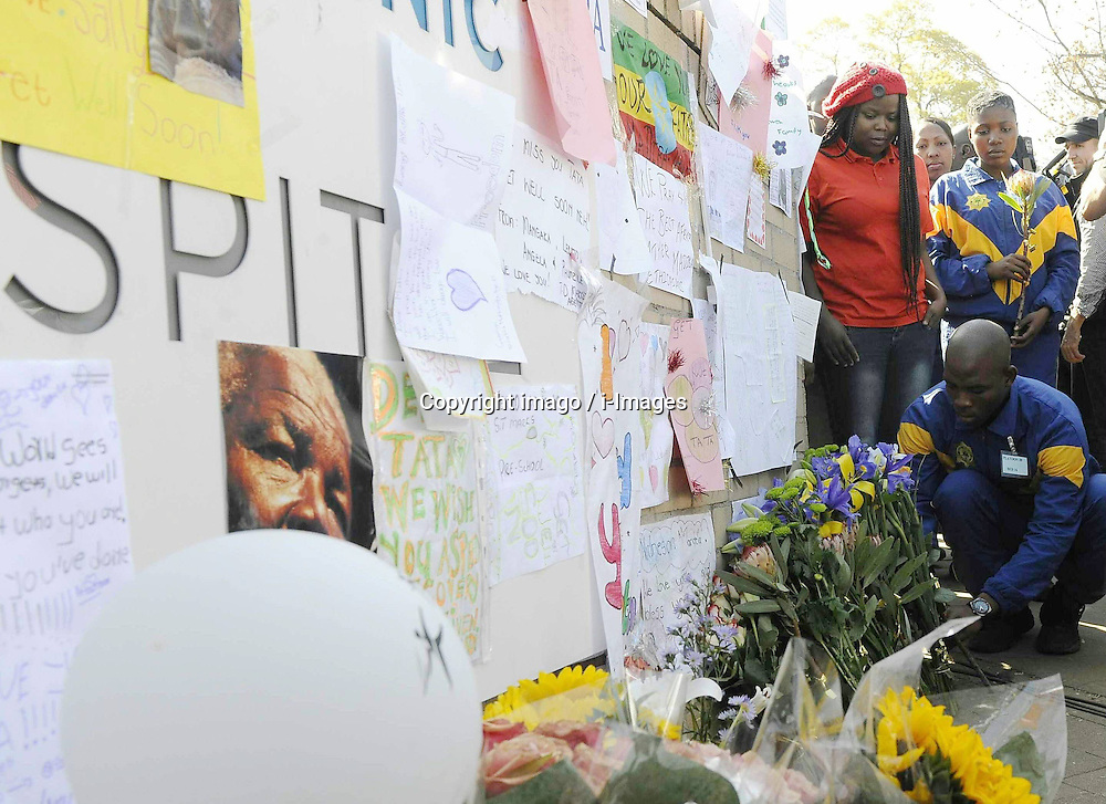 File Photo- Nelson Mandela Dead: Former South African President Has Died At 95. The former South African president had been suffering from a recurring lung infection, Thursday December 05, 2013.<br /> 59900844<br /> A Police officer presents flowers to former South African president Nelson Mandela outside the hospital where Mandela is treated in Pretoria, South Africa, on June 25, 2013. South Africans on Monday were holding their breath over former President Nelson Mandela's health that has deteriorated from serious to critical. Mandela, 94, has been hospitalised for a recurring lung problem since June 8 2013. Pretoria, South Africa, on June 25, 2013. Picture by imago / i-Images<br /> UK ONLY