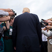 """July 6, 2015 - New York, NY : Businessman and GOP presidential candidate Donald Trump, with back to camera, speaks with members of the media as he arrives at the Trump Golf Links on Monday afternoon.  Hank Steinbrenner (not pictured) hosted the first annual """"Hank's Yanks Golf Classic,"""" a charity golf tournament, at the newly opened Trump Golf Links at Ferry Point in the Bronx on Monday afternoon. CREDIT: Karsten Moran for The New York Times"""