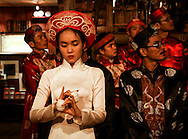 A young woman plays music with tea cups while a group of men behind her watch something off to the side, Dalat, Lam Dong Province, Vietnam, Southeast Asia