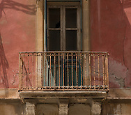 A rusty iron balcony on a pink building in Ortigia, Syracuse, Sicily, Italy
